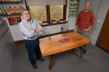 Two men standing on either side of polished conference table